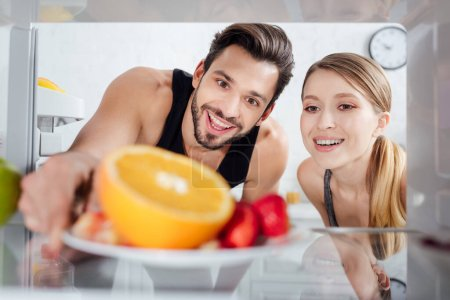 Photo for Selective focus of happy man and woman looking at tasty fruits in fridge - Royalty Free Image