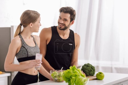 Photo for Happy man cooking near woman with glass of smoothie in kitchen - Royalty Free Image