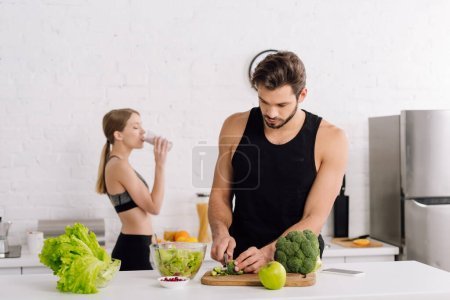 Photo for Selective focus of handsome man cooking near girl drinking smoothie - Royalty Free Image