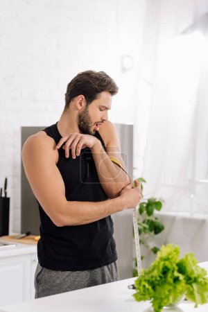 Photo for Selective focus of surprised man measuring muscle on hand in kitchen - Royalty Free Image
