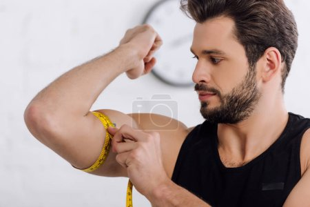 Photo for Handsome and sportive man measuring muscle on hand - Royalty Free Image