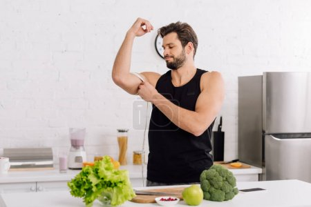 Photo for Handsome and sportive man measuring muscle on hand near fresh food - Royalty Free Image