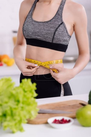cropped view of sportive girl measuring waist near fresh food in kitchen