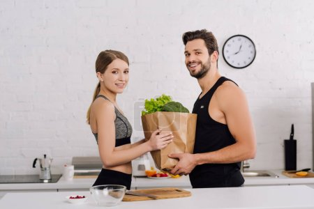 Photo for Happy girl and bearded man holding paper bag with groceries in kitchen - Royalty Free Image