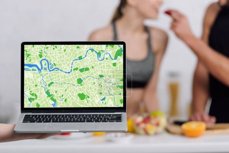 selective focus of laptop with online map near couple in kitchen
