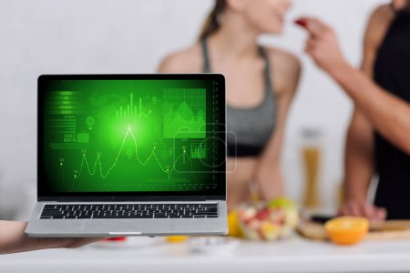 selective focus of laptop with graphs on screen near couple in kitchen