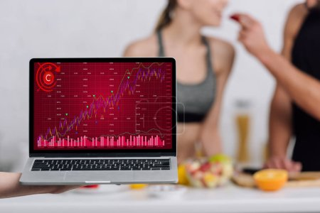 selective focus of laptop with graphs on screen near man and woman in kitchen