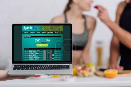 Photo pour Foyer sélectif de l'ordinateur portable avec site de paris sportifs à l'écran près du couple dans la cuisine - image libre de droit