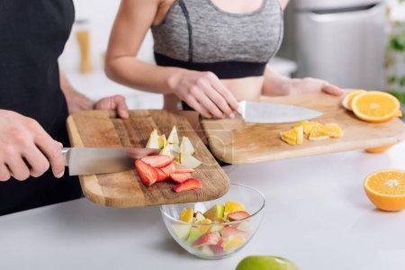 Foto de Vista panorámica del hombre y la mujer que cocinan ensalada de frutas - Imagen libre de derechos