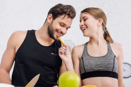 selective focus of happy girl feeding cheerful man with sliced orange