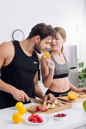selective focus of sportive girl feeding bearded man with orange