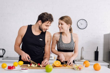 Photo for Cheerful couple smiling while preparing fruit salad - Royalty Free Image