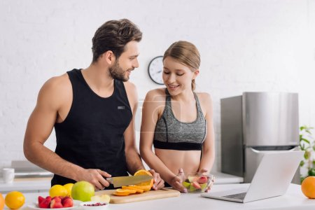 Photo for Happy girl with salad near sportive man, laptop and fruits in kitchen - Royalty Free Image