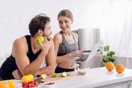 Photo pour Homme heureux avec pomme regardant femme avec ordinateur portable près des fruits - image libre de droit