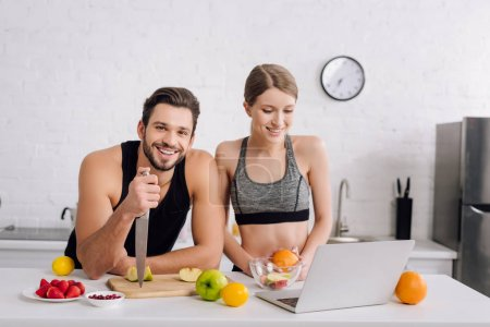 Photo for Happy man with knife near fruits, woman and laptop - Royalty Free Image