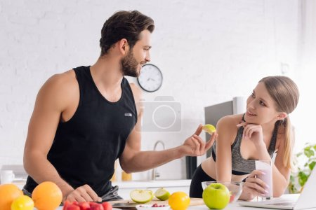 Photo for Happy man with sliced apple near girl with smoothie and laptop - Royalty Free Image