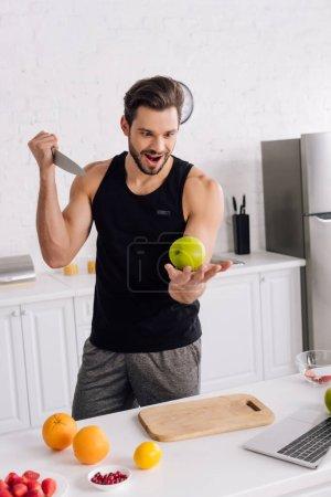 Photo pour Bel homme avec couteau tenant pomme près des fruits et ordinateur portable - image libre de droit