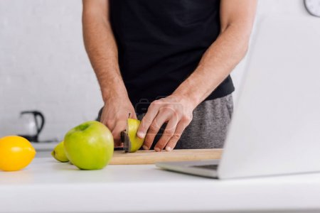 Photo for Cropped view of man cutting apple near laptop at home - Royalty Free Image