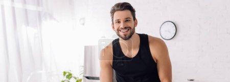 panoramic shot of happy bearded man looking at camera