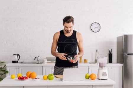 handsome man looking at laptop near tasty fruits and blender with smoothie