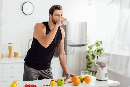 Photo for Bearded man drinking fresh smoothie near blender and fruits - Royalty Free Image