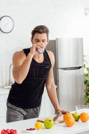 Photo pour Bel homme buvant smoothie près de fruits frais - image libre de droit