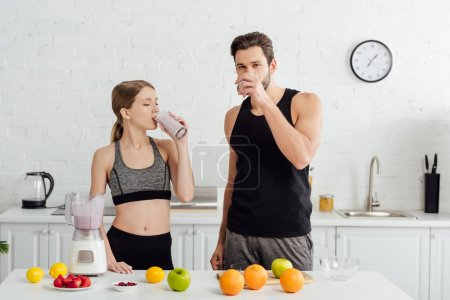 Photo for Sportive man and woman drinking tasty smoothie near fruits - Royalty Free Image