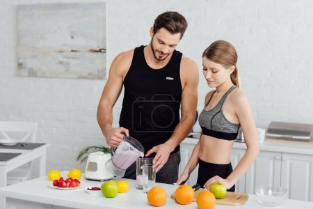 Sportlicher Mann gießt Smoothie in Glas neben attraktiver Frau und Früchten