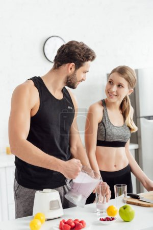 sportive man pouring smoothie in glass near cheerful woman and fruits