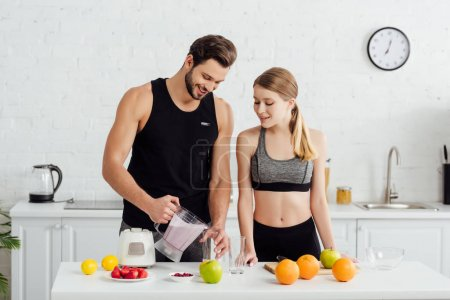 sportive man holding blender with smoothie near happy girl and fruits