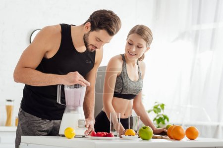 Photo for Sportive man preparing smoothie near happy girl and fruits - Royalty Free Image
