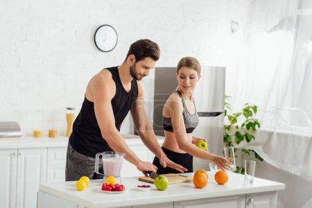Photo pour Bel homme cuisine près de fille sportive et mélangeur avec smoothie - image libre de droit