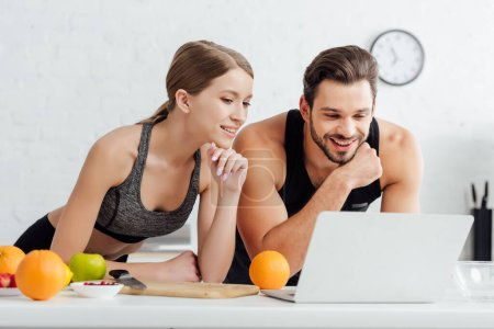 Photo for Happy man and woman looking at laptop near tasty fruits - Royalty Free Image