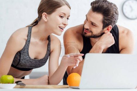 sportive girl pointing with finger at laptop near happy man