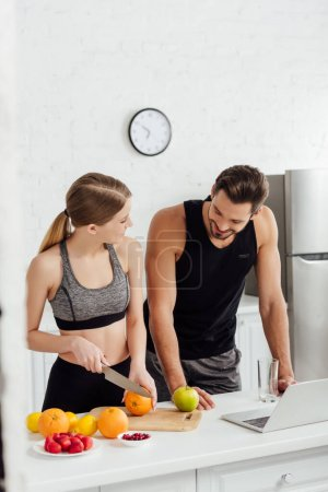 Photo for Sportive girl cutting orange near man and laptop - Royalty Free Image