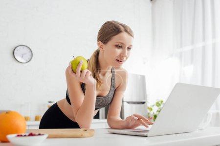 Selektiver Fokus der sportlichen Frau mit leckerem Apfel und Laptop