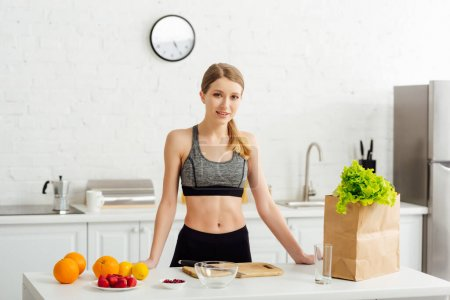 Photo for Happy woman in sportswear near paper bag and fruits in kitchen - Royalty Free Image
