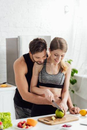 Photo pour Couple heureux en vêtements de sport coupe pomme sur planche à découper - image libre de droit