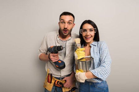 Photo for Surprised manual workers holding paint can, brushes and electric drill on grey - Royalty Free Image