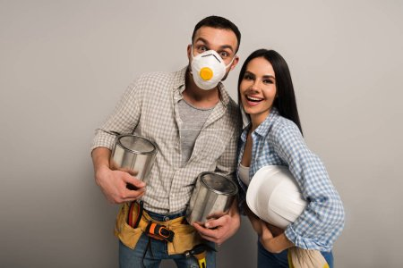Photo for Excited manual workers in safety mask holding paint cans and helmet on grey - Royalty Free Image