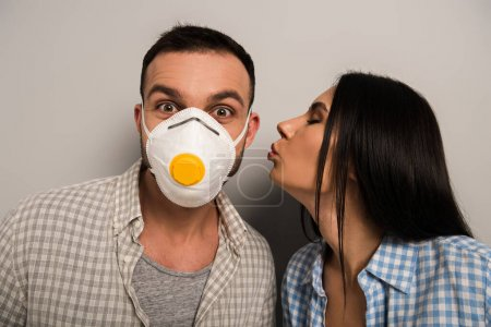 Photo pour Femme embrasser heureux ouvrier en masque de sécurité sur gris - image libre de droit