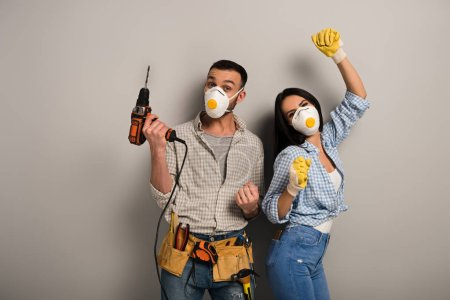Photo for Happy manual workers in safety masks holding electric drill on grey - Royalty Free Image