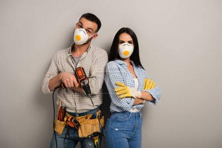 Photo pour Travailleurs manuels confiants masques de sécurité tenant la perceuse électrique en gris - image libre de droit