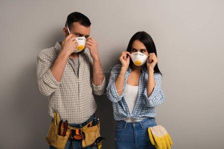 Photo pour Ouvriers portant des masques de sécurité sur fond gris - image libre de droit