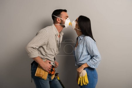 happy manual workers kissing in safety masks on grey