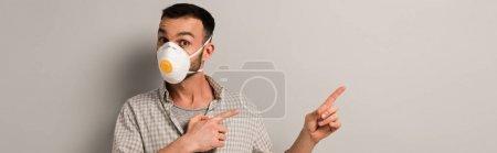 Photo pour Prise de vue panoramique de l'ouvrier surpris en masque de sécurité pointant sur le gris - image libre de droit
