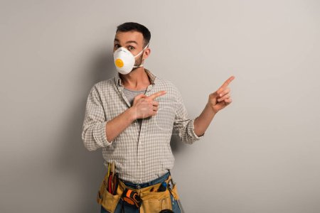 Photo for Emotional manual worker in safety mask with tool belt pointing on grey - Royalty Free Image