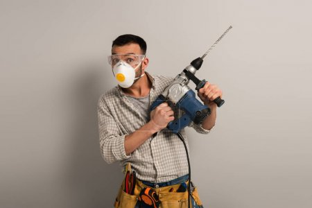 Photo for Surprised foreman in safety mask holding electric drill on grey - Royalty Free Image