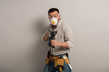 Photo pour Contremaître émotionnel en masque de sécurité tenant le drill électrique sur gris - image libre de droit