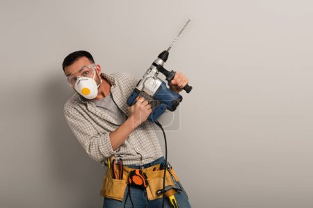Photo pour Scared workman in safety mask holding electric drill on grey - image libre de droit